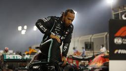 Pembalap Mercedes asal Inggris, Lewis Hamilton berlutut saat keluar dari mobilnya, sebagai dukungan kampanye gerakan Black Lives Matter, usai memenangi Grand Prix Formula Satu Bahrain di Sirkuit Internasional Bahrain, Sakhir, Minggu, (29/11/2020). (AFP/Hamad I Mohammed)