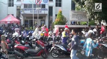 Ribuan warga Bogor mengantre E-KTP di Disdukcapil setempat. Penuhnya tempat membuat masyarakat antre hingga ke jalan raya.