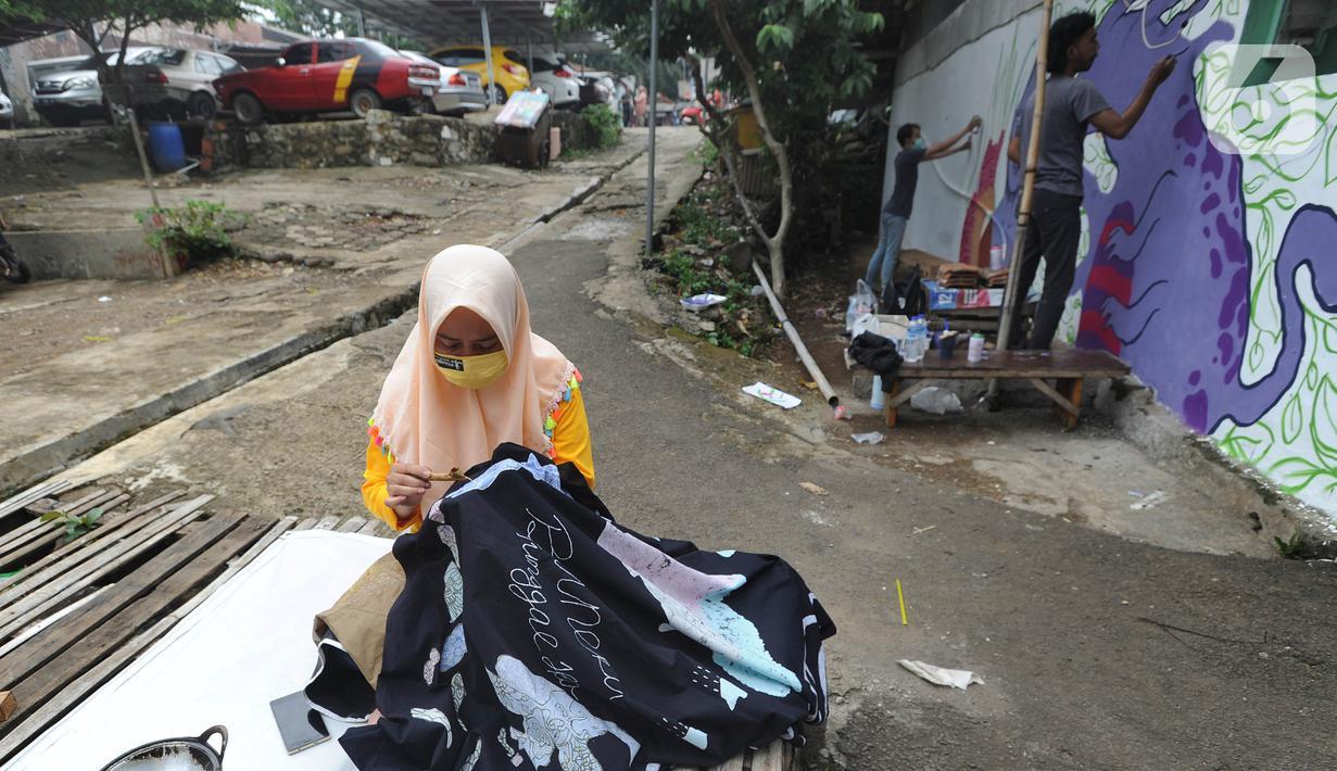 Warga menyelesaikan pembuatan batik tulis saat pelaksanaan kegiatan mural Raincity Strike #8 di Kampung Batik Cibuluh, Bogor, Minggu (22/11/2020). Kegiatan seni mural ini melibatkan puluhan seniman mural se-Jabodetabek di kampung batik. (merdeka.com/Arie Basuki)