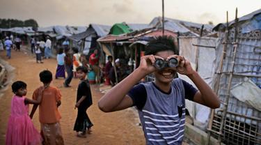 Seorang bocah Rohingya melihat melalui teropong mainan pada perayaan Idul Adha di kamp pengungsi Kutupalong, Bangladesh, Rabu (22/8). Hampir setahun mereka menghuni kamp ini usai kabur menghindari represi militer di Negara Bagian Rakhine. (AP/Altaf Qadri)