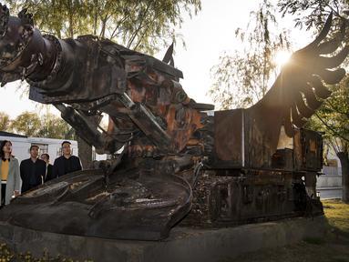Para wisatawan mengamati patung yang terbuat dari peralatan tambang di taman industri budaya Zhongneng, Kota Yulin, Provinsi Shaanxi, China, 19 Oktober 2020. Taman industri budaya bertema batu bara tersebut baru-baru ini telah dibuka untuk umum. (Xinhua/Tao Ming)