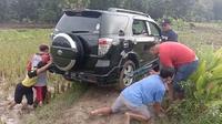 Mobil Rizki yang tersesat di sawah saat dievakuasai warga. (Ahmad Adirin/Liputan6.com)