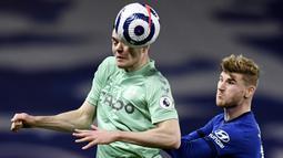 Striker Chelsea, Timo Werner, duel udara dengan pemain  Everton, Michael Keane, pada laga Liga Inggris di Stadion Stamford Bridge, Senin (8/3/2021). Chelsea menang dengan skor 2-0. (Glyn Kirk/Pool via AP)