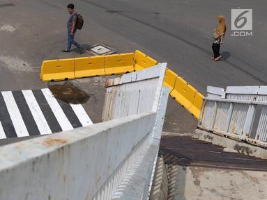 Pejalan kaki melintas di dekat tangga JPO yang berada di tengah jalan Dewi Sartika, Jakarta, Rabu (9/1). Adanya proyek pelebaran jalan menyebabkan posisi trotoar bergeser sehingga tangga JPO menjadi di tengah jalan. (Liputan6.com/Immanuel Antonius)