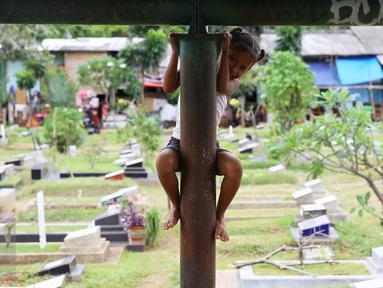 Seorang anak bermain di sekitar TPU Karet Bivak, Jakarta, Jumat (13/1). Semakin berkurangnya lahan hijau menyebabkan anak-anak di Ibukota terpaksa bermain di tempat yang tidak semestinya. (Liputan6.com/Immanuel Antonius)