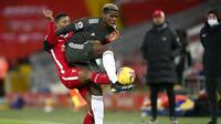 Pemain Manchester United, Paul Pogba, berebut bola dengan pemain Liverpool, Georginio Wijnaldum, pada laga Liga Inggris di Stadion Anfield, Minggu (17/1/2021). Kedua tim bermain imbang 0-0. (Michael Regan/Pool via AP)