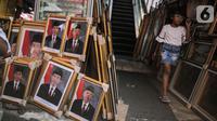 Seorang anak melintas di antara bingkai foto Presiden Jokowi dan Wakil Presiden terpilih Ma'ruf Amin yang dijualnya di Pasar Baru, Jakarta, Rabu (16/10/2019). Menjelang pelantikan presiden, foto pasangan Jokowi-Ma'ruf Amin mulaih dijual ke pasar umum. (Liputan6.com/Faizal Fanani)
