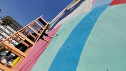 Tarsila Schubert menggunakan tangga membuat karya mural di dinding Museum Seni Terbuka, Kota Amman, Yordania, Kamis (29/9). Mural karya Tarsila Schubert asal Brasil itu menghiasi Museum Seni Terbuka, Kota Amman, Yordania. (REUTERS/Muhammad Hamed)