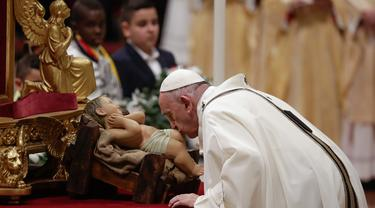 Paus Fransiskus mencium patung bayi Yesus ketika memimpin misa Malam Natal di Basilika Santo Petrus, Vatikan, Selasa (24/12/2019). Paus Fransiskus memimpin Natal bagi 1,3 miliar umat Katolik dunia. (AP Photo/Alessandra Tarantino)