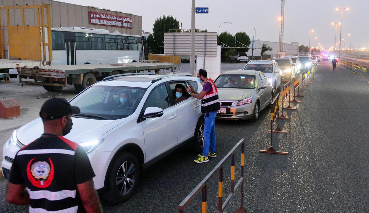 Petugas medis mendata orang-orang yang antre memasuki sebuah stasiun pengujian lantatur (drive thru) baru untuk COVID-19 di Kegubernuran Mubarak Al-Kabeer, Kuwait, 20 September 2020. Kuwait membuka stasiun pengujian PCR lantatur baru untuk memperluas kapasitas pengujian COVID-19. (Xinhua/Asad)