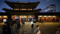 Gambar pada 4 Oktober 2019 memperlihatkan wisatawan saat kunjungan malam ke Istana Gyeongbokgung di pusat Seoul, Korea Selatan. Kunjungan malam tersedia pada minggu ketiga dan keempat setiap bulan mulai dari 26 April sampai 31 Oktober, kecuali pada bulan Agustus. (Photo by Ed JONES / AFP)