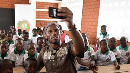 Mantan penyerang Chelsea, Didier Drogba berswafoto dengan murid-murid selama peresmian sekolah yang disponsori dirinya di Pokou-Kouamekro, dekat Gagnoa, Pantai Gading tengah barat (17/1). (AFP Photo/Sia Kambou)