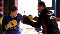 Petinju wanita Albania, Elsidita Selaj, melakukan sesi latihan bersama pelatihnya, Jetmir Kuci, di Shkodra, Kamis (21/1/2021). Tekad yang kuat membuat wanita berusia 20 tahun ini menjadi petinju wanita pertama di Albania. (AFP/Gent Shkullaku)