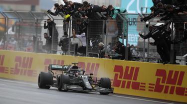 Pembalap Mercedes dari Inggris Lewis Hamilton disambut para kru setelah melewati garis finis F1 GP Turki di sirkuit balap Istanbul Park di Istanbul, Minggu (15/11/2020). Pebalap Formula 1 Lewis Hamilton resmi meraih juara dunia Formula 1 2020. (Tolga Bozoglu/Pool via AP)