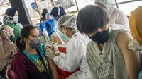 Warga menerima vaksin virus corona COVID-19 Sinovac di klinik vaksinasi massal darurat di lapangan sepak bola di Surabaya, Jawa Timur, Selasa (6/7/2021). Indonesia tengah memerangi gelombang infeksi baru yang belum pernah terjadi sebelumnya. (JUNI KRISWANTO/AFP)
