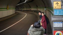 Pasangan berpose untuk foto di sebuah terowongan yang ditampilkan dalam film berjudul 'Parasite', di Seoul pada 13 Februari 2020. Lokasi syuting Parasite di Korea Selatan semakin ramai dikunjungi turis setelah film tersebut berhasil memboyong dan mendominasi di penghargaan Oscar 2020. (Ed JONES/AFP)