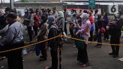 Calon penumpang KRL antre untuk masuk ke dalam Stasiun Bekasi, Jawa Barat, Senin (1/2/2021). Mereka mengantre dengan penjagaan ketat petugas keamanan Stasiun Bekasi. (Liputan6.com/Herman Zakharia)