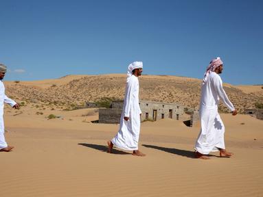 Mantan penduduk Wadi al-Murr berjalan dekat rumah-rumah terlantar di Desa Omani, Wadi al-Murr, Oman, 31 Desember 2020. Pasir yang menggunung hanya menyisakan sedikit bukti bahwa Desa Omani pernah ada di Wadi al-Murr, Oman. (MOHAMMED MAHJOUB/AFP)