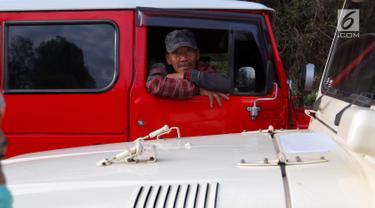 Sopir jeep menunggu wisatawan yang akan melanjutkan perjalanan ke Gunung Bromo di Kecamatan Tosari, Pasuruan, Jawa Timur, Sabtu (4/11). Mobil ini mampu membawa 5 penumpang. (Liputan6.com/Fery Pradolo)