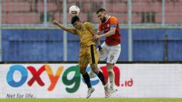 Pemain Borneo FC Samarinda, Javlon Guseynov, berebut bola dengan pemain Bhayangkara Solo FC, Dendy Sulistyawan (kiri), dalam pertandingan Babak Penyisihan Grup B Piala Menpora 2021 di Stadion Kanjuruhan, Malang. Senin (22/3/2021). (Bola.com/Arief Bagus)