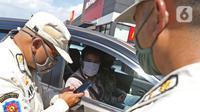 Petugas melihat hasil rapid test antigen pengemudi di Rest Area KM 57, Tol Jakarta-Cikampek, Karawang, Jawa Barat, Kamis (24/12/2020). Warga yang tidak memiliki surat keterangan non reaktif Covid-19 diminta untuk melakukan rapid test antigen ditempat yang disediakan. (Liputan6.com/Herman Zakharia)