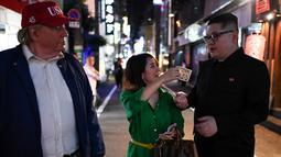 Seorang wanita memberikan uang 1.000 yen untuk berswafoto dengan peniru pemimpin Korea Utara Kim Jong-un dan peniru Presiden AS, Donald Trump selama KTT G20 di Osaka, Jepang, Jumat (28/6/2019). Sejumlah pemimpin dunia berkumpul dalam KTT G20 yang berlangsung dua hari di Osaka (Charly TRIBALLEAU/AFP)