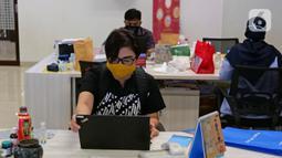 Karyawan membuka laptop sebelum memulai aktivitas bekerja di Suntory Garuda, Jakarta, Senin (8/8/2020). Perusahaan tersebut menerapkan protokol kesehatan saat hari pertama kerja di masa PSBB transisi yang diterapkan oleh Pemprov DKI Jakarta. (Liputan6.com/Herman Zakharia)