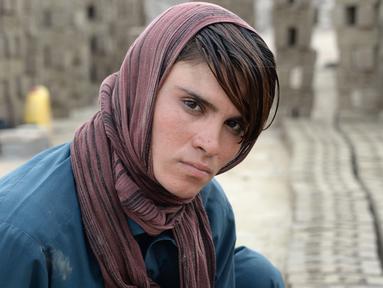 Foto pada 11 Maret 2018 memperlihatkan perempuan Afghanistan, Sitara Wafadar (18) yang menyamar sebagai laki-laki saat bekerja di pabrik batu bata di Provinsi Nangarhar. Sitara merindukan rambut panjang seperti gadis-gadis lain. (NOORULLAH SHIRZADA/AFP)