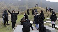 Reaksi para pelayat saat pemakaman korban yang meninggal karena COVID-19 di sebuah pemakaman pinggiran Kota Ghaemshahr, Iran, 16 Desember 2020. Sejak kasus pertama 19 Februari lalu, jumlah infeksi COVID-19 di Iran telah mencapai 1.138.550 kasus dengan 53.093 korban jiwa. (AP Photo/Ebrahim Noroozi)