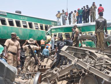 Tim penyelamat dan penduduk setempat berkumpul di dekat kecelakaan yang terjadi antara dua kereta di distrik Rahim Yar Khan, Pakistan, Kamis (11/7/2019). Insiden ini menyebabkan setidaknya sembilan orang tewas dan lebih dari 60 lainnya luka-luka. (AP Photo/Waleed Saddique)