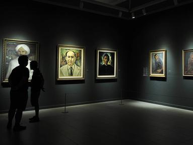 """Pengunjung melihat sejumlah lukisan koleksi Istana Kepresidenan yang dipamerkan di Galeri Nasional, Jakarta, Senin (6/8). Pameran ini bertajuk """"Indonesia Semangat Dunia"""". (Merdeka.com/Iqbal Nugroho)"""