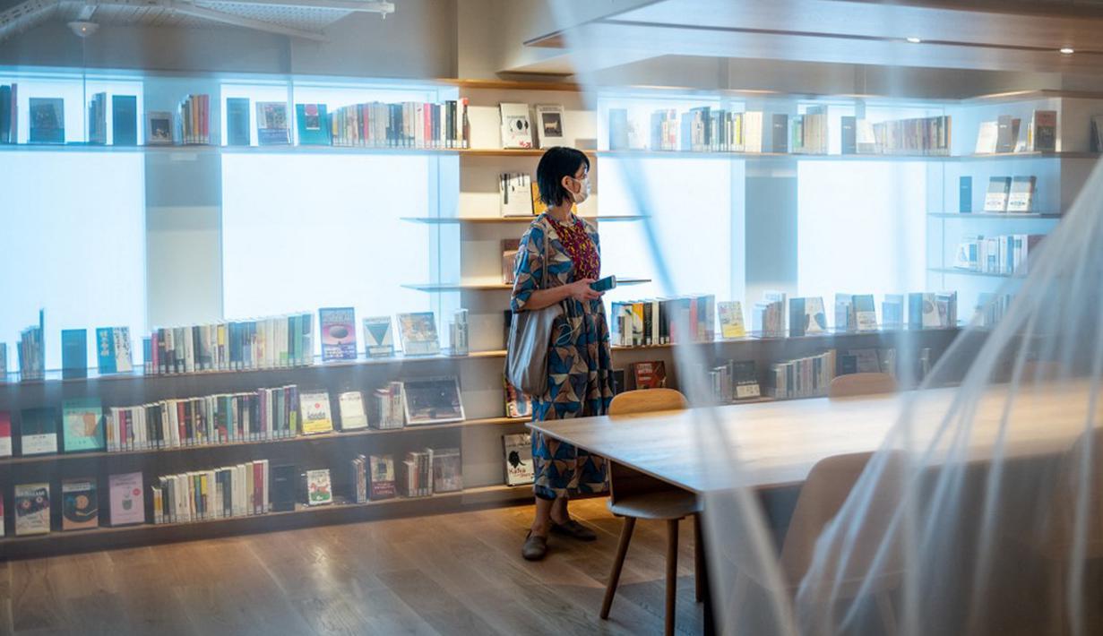 Seorang reporter berdiri dalam Rumah Sastra Internasional Waseda di Universitas Waseda, Tokyo, Jepang, 22 September 2021. Rumah Sastra Internasional Waseda yang juga dikenal sebagai Perpustakaan Haruki Murakami dirancang oleh arsitek Jepang, Kengo Kuma. (Philip FONG/AFP)