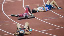 Para pelari tampak lelah usai menyelesaikan lomba pada nomor 400 meter gawang cabang atletik Asian Games XVIII di SUGBK, Jakarta, Minggu (26/8/2018). (Bola.com/Vitalis Yogi Trisna)