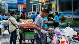 Seorang pedagang menyiapkan buah di jalan di Bangkok, Thailand (20/9). Menurut Narumol Nirathron dari Universitas Thammasat dalam laporan International Labour Organization, PKL makanan di Bangkok sudah ada sejak 200-an tahun lalu. (AFP Photo/Jewel Samad)