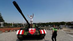 Suporter Red Star Belgrade berpose di tank T-55 yang terparkir di tribun utara Stadion Rajko Mitic, Belgrade, Serbia, Selasa (27/8/2019). Kehadiran tank itu hanya selang sepekan dari penyerangan etnis Serbia yang tengah nonton bareng leg pertama di salah satu bar Kroasia. (AP Photo/Darko Vojinovic)