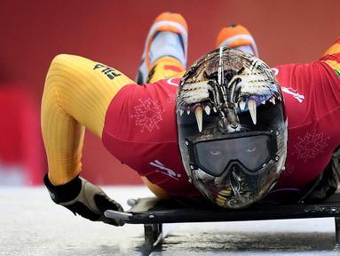 Atlet balap kereta salju, Akwasi Frimpong dari Ghana memulai sesi latihan pada Olimpiade Musim Dingin Pyeongchang 2018 di Olympic Sliding Center di Pyeongchang, Korsel (21/2). Akwasi memakai helm dengan design kepala harimau. (AFP Photo/Mark Ralston)