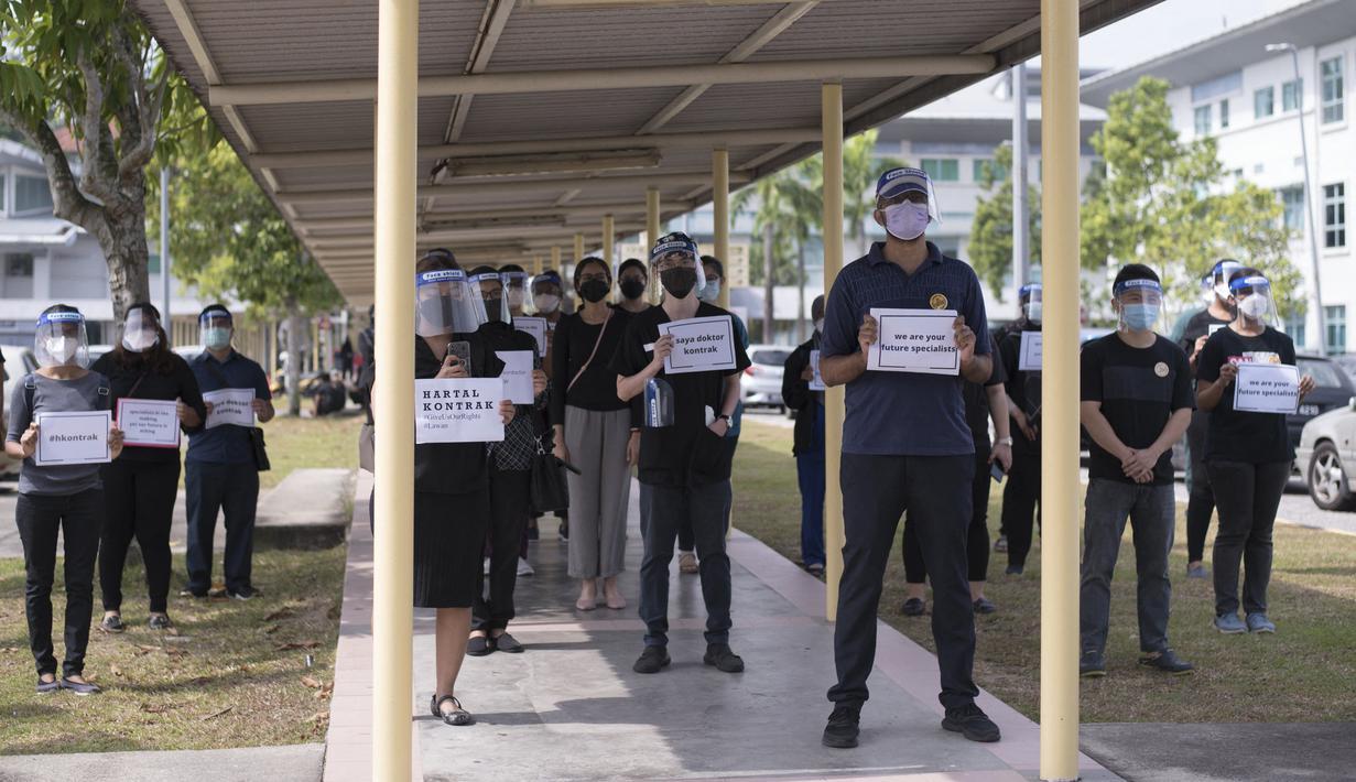 Dokter kontrak memegang plakat saat berpartisipasi dalam aksi mogok di Rumah Sakit Sungai Buloh di Selangor, Malaysia, Senin (26/7/2021). Ratusan dokter melakukan aksi mogok kerja dari rumah sakit pemerintah Malaysia pada (26/7). (AFP/Arif Kartono)