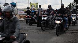 Pengendara motor melewati perlintasan kereta api tanpa palang pintu di kawasan Kelingkit, Rawa Buaya, Jakarta, Selasa (26/2). Warga setempat melakukan penjagaan swadaya agar perlintasan tanpa palang pintu tidak membahayakan. (Liputan6.com/Johan Tallo)