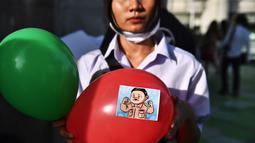Seorang pengunjuk rasa memegang balon, dengan stiker yang menggambarkan Perdana Menteri Thailand Prayut Chan-O-Cha sebagai Adolf Hitler, selama demonstrasi menentang usulan pembelian kapal selam oleh pemerintah yang berpihak pada militer di Bangkok (31/8/2020). (AFP/Lillian Suwanrumpha)