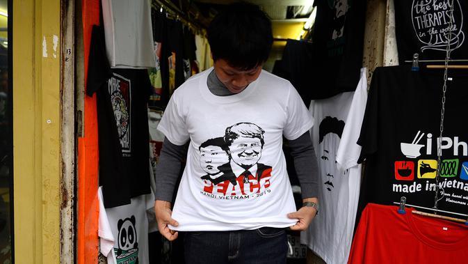 Warga mencoba kaus bergambar wajah Presiden AS Donald Trump dan pemimpin Korea Utara Kim Jong-un di sebuah toko di Hanoi, Jumat (22/2). Pembuatan kaus itu menyambut KTT kedua AS-Korea Utara di Vietnam pada 27 Februari mendatang. (Nhac NGUYEN/AFP)