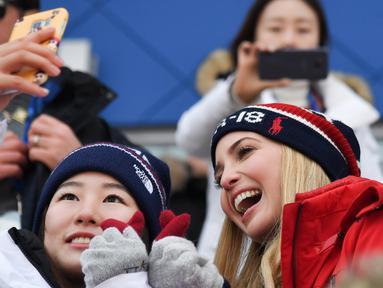 Putri Presiden AS Donald Trump yang juga penasihat senior Gedung Putih, Ivanka Trump (kanan) berswafoto dengan atlet Korea Selatan saat menonton snowboard pria pada Olimpiade Musim Dingin Pyeongchang 2018, Korea Selatan, Sabtu (24/2). (Ed JONES/AFP)