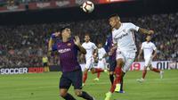 Striker Barcelona, Luis Suarez, duel udara dengan bek Sevilla, Guilherme Arana, pada laga La Liga Spanyol di Stadion Camp Nou, Barcelona, Sabtu (20/10). Barcelona menang 4-2 atas Sevilla. (AFP/Lluis Gene)