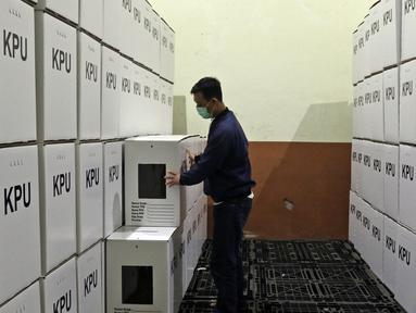 Petugas memeriksa kotak suara yang telah dirakit di Gudang Logistik KPU, Depok, Jawa Barat, Jumat (13/11/2020). KPU Kota Depok telah merakit 4.015 kotak suara serta menyediakan 16.060 bilik suara yang akan digunakan untuk Pilkada Kota Depok pada 9 Desember 2020. (Liputan6.com/Herman Zakharia)