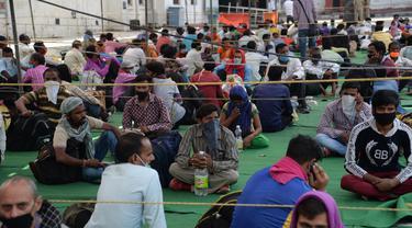 Para buruh migran menunggu untuk menaiki kereta khusus menuju rumah mereka saat masa karantina wilayah (lockdown) nasional diterapkan demi mencegah penyebaran COVID-19 di Jalandhar, Negara Bagian Punjab, India utara, (5//5/2020). (Xinhua/Stringer)