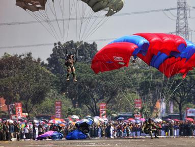 Prajurit TNI melakukan atraksi terjun payung pada perayaan HUT ke-74 TNI di Taxy Way Echo Lanud Halim Perdanakusuma, Jakarta Timur, Sabtu (5/10/2019). Selain terjun payung, HUT ke-74 TNI juga menampilkan atraksi bela diri prajurit. (Liputan6.com/JohanTallo)