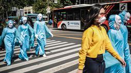 Massa menggelar aksi teatrikal di Pelican crossing di Jakarta, Kamis (20/12). Mereka mengajak pemilih milenial untuk memilih pemimpin yang berorientasi jangka panjang dan berpihak pada energi bersih, adil, dan berkelanjutan. (Liputan6.com/Faizal Fanani)