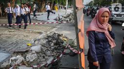 Pelajar melintasi trotoar yang sedang direvitalisasi di kawasan Kramat Raya, Jakarta, Rabu (6/11/2019). Ketua Koalisi Pejalan Kaki Alfred Sitorus menilai pengerjaan revitalisasi trotoar membahayakan pejalan kaki karena tidak ada ruang sementara untuk melintas. (Liputan6.com/Faizal Fanani)