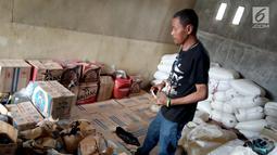Seorang pria memeriksa barang bukti minuman keras Cap Tikus di Polres Gorontalo, Kamis, (24/1). Sebanyak 1,5 ton Cap Tikus dalam kantong plastik diselundupakan dalam karung. (Liputan6.com/Arfandi Ibrahim)