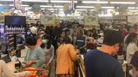 Orang-orang antre untuk membayar makanan dan belanjaan lainnya di supermarket 24 jam di Yangon, Selasa (24/3/2020). Tanggapi kasus pertama Corona COVID-19 pada Senin 23 Maret malam, warga Myanmar memadati pusat perbelanjaan untuk menyetok kebutuhan pokok dan persedian makanan. (AP/Thein Zaw)