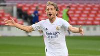 Gelandang Real Madrid, Luka Modric, melakukan selebrasi usai mencetak gol ke gawang Barcelona pada laga lanjutan Liga Spanyol di Camp Nou Stadion, Sabtu (24/10/2020) malam WIB. Real Madrid menang 3-1 atas Barcelona. (AFP/Lluis Gene)